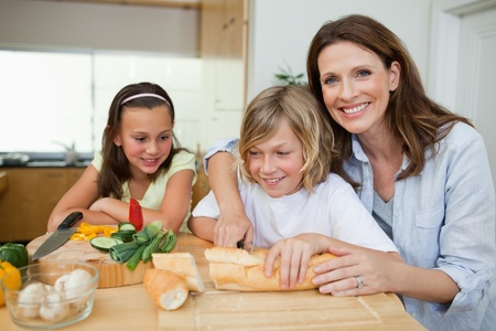 Mother making sandwiches together with her children photo