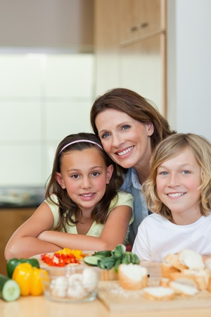 Smiling siblings and mother making sandwiches together photo