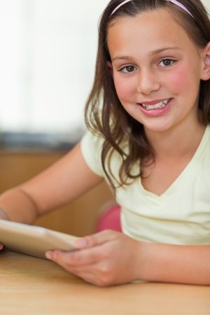 Girl sitting at the table with tablet Stock Photo - 11685423