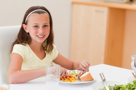 Smiling girl having dinner at the dinner table photo