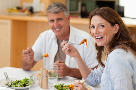 Laughing couple eating dinner together photo