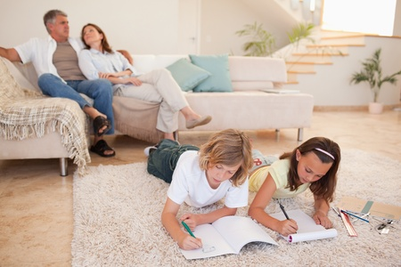 Siblings doing their homework on the floor with parents behind them photo