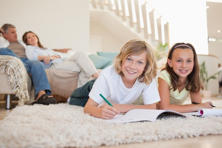 Brother and sister doing their homework on the floor Stock Photo - 11685594