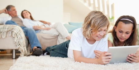 home entertainment: Siblings with tablet lying on the floor Stock Photo