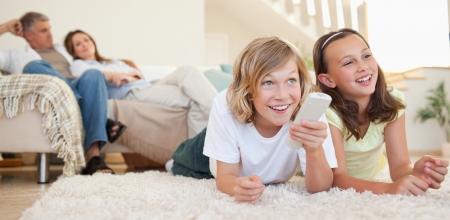 Siblings lying on the floor watching tv together photo