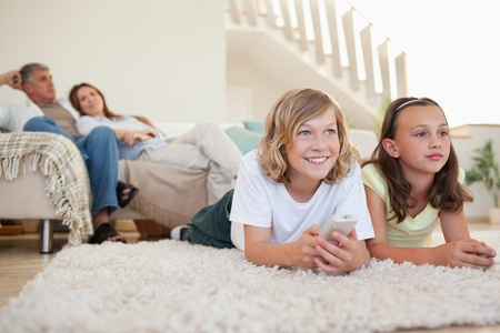 Siblings lying on the carpet watching tv together photo