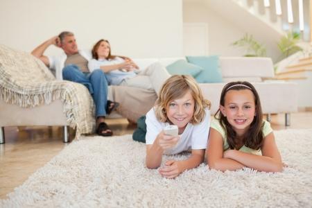 Hermanos en la alfombra viendo la televisión juntos