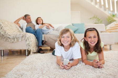 Siblings on the floor watching tv together photo