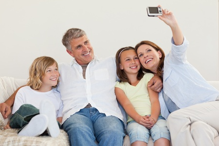 Mother taking a family picture on the couch photo