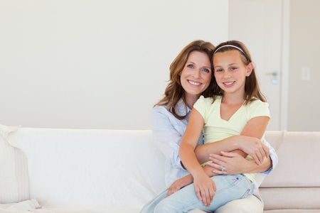 Happy smiling mother and daughter embracing photo