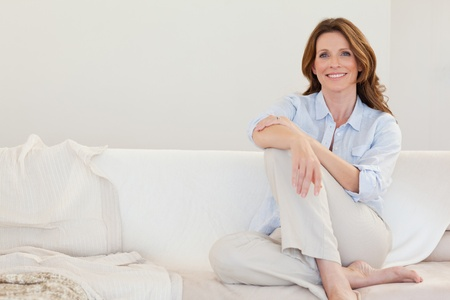Smiling mature woman sitting on her sofa photo