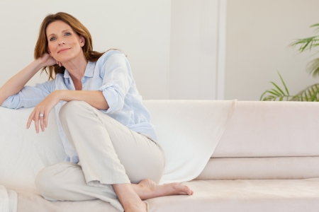 attractive couch: Mature woman in thoughts on the sofa Stock Photo