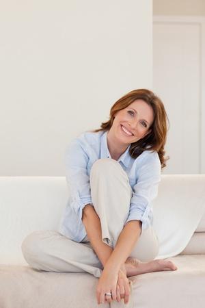 sch�ne frauen: Smiling reife Frau auf ihrer Couch sitzend