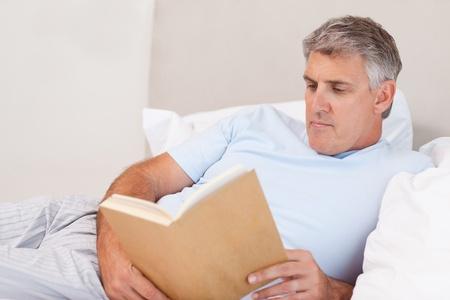 Mature man reading book in the bed Stock Photo - 11685299