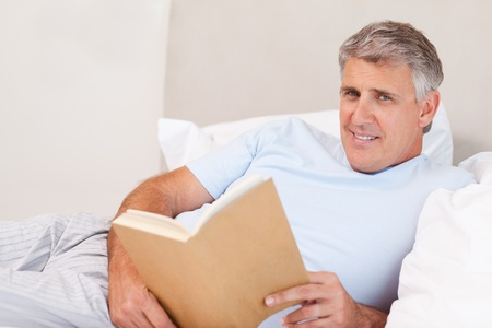 Smiling man with book in the bed Stock Photo - 11685210