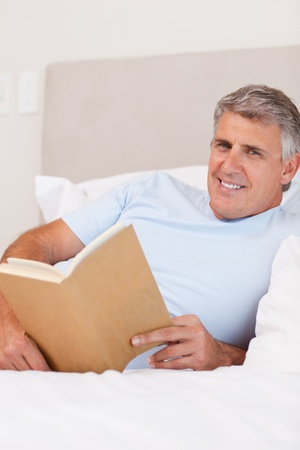 Smiling man reading in the bed Stock Photo - 11685774