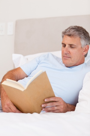 Man reading book in his bed photo
