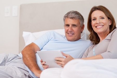 Couple with tablet in the bed photo