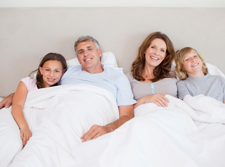 Happy family about to take a nap together photo