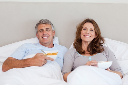 early 40s: Mature couple eating cereals in bed