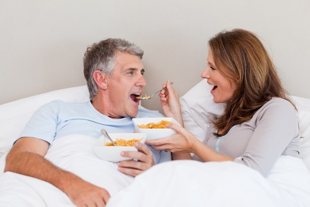 early 40s: Mature couple eating cereals in their bed