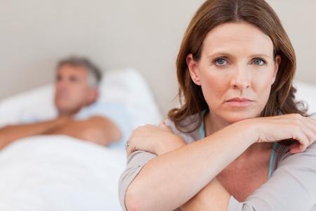gente triste: Triste mujer en la cama con su marido en el fondo
