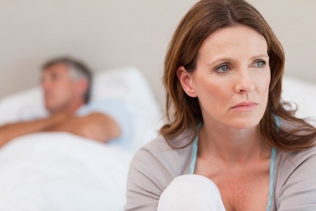 Sad mature woman on bed with her husband in the background Stock Photo