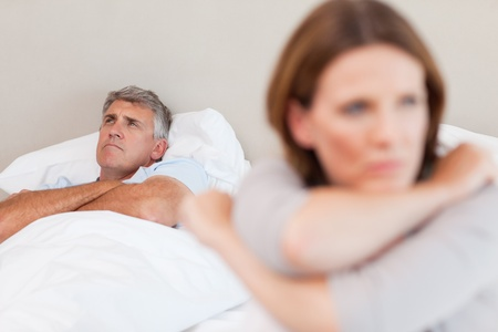 disagreeing: Sad man in the bed with his wife in the foreground