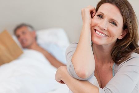 mujeres maduras: Mujer sonriente feliz en la cama con la lectura marido detr�s de ella
