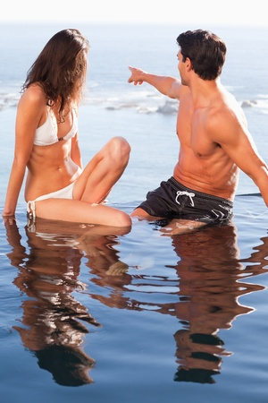 Young couple in the pool looking at the sea photo