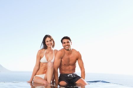Smiling couple sitting on the pool edge photo
