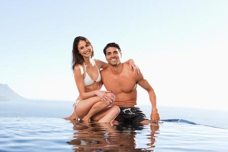 Happy couple sitting on the pool edge Stock Photo - 11686607