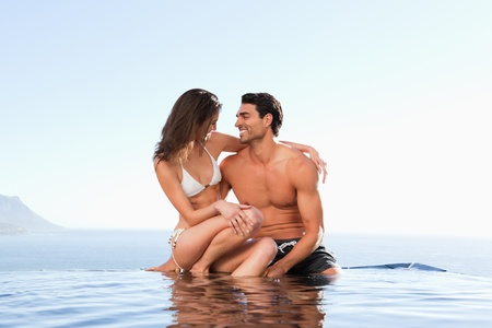 Couple sitting on the pool edge together photo