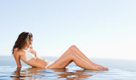 poolside: Woman laying on the pool edge enjoying the sun Stock Photo
