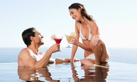 Happy couple having cocktails in the pool photo