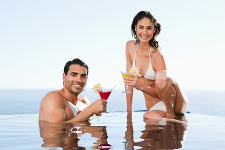 Cheerful young couple having cocktails in the pool photo