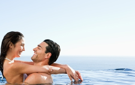 Young couple embracing in the pool photo