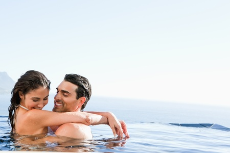 Young couple hugging in the pool photo