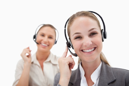 Joyful operators using headsets against a white background Stock Photo - 11686682