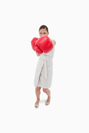 Portrait of a serious businesswoman punching someone against a white background photo