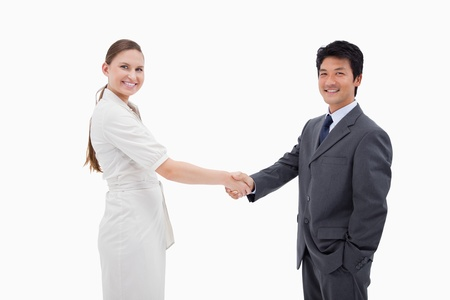 Two business people shaking hands against a white background photo