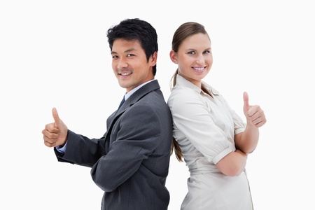 Business people standing back to back with the thumb up against a white background photo