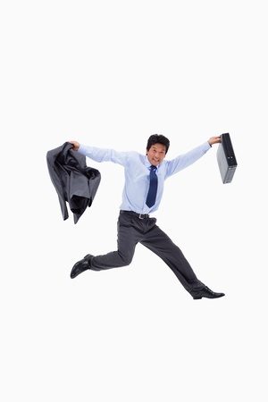 Cheerful businessman jumping while holding his jacket and a briefcase against a white background photo