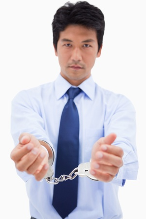 Portrait of a businessman with handcuffs against a white background photo