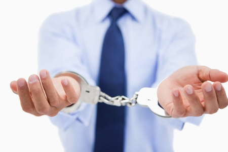 Close up of a professionals hands with handcuffs against a white background photo