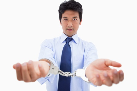 Businessman with handcuffs against a white background photo
