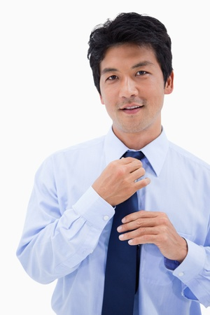 Portrait of a smiling businessman fixing his tie against a white background photo