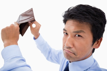 empty wallet: Broke businessman showing his empty wallet against a white background