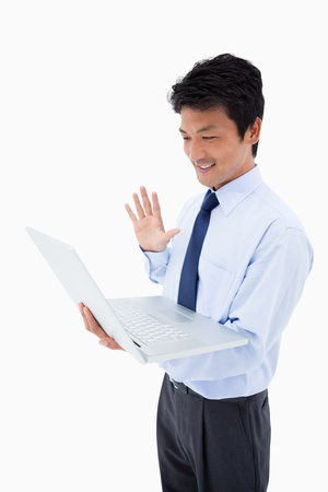 Portrait of a businessman waving at a laptop against a white background photo