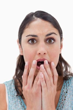 faccia disperata: Ritratto di una donna scioccata gesticolare contro uno sfondo bianco